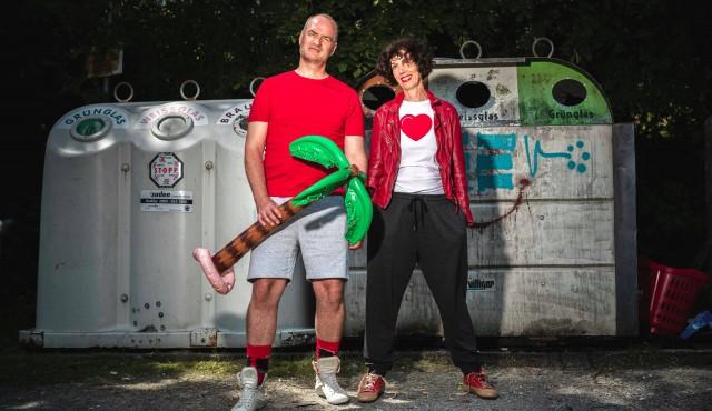 Birgit und Wolfgang mit aufblasbarer Palme in der Hand vor Altglascontainer.