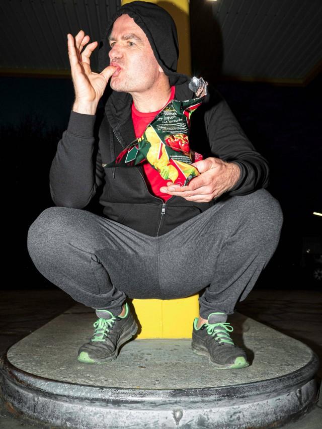 Wolfgang hockt Nachts im schwarzen Hoody an der Zapfsäule und leckt sich Chipskrümel von den Fingern.